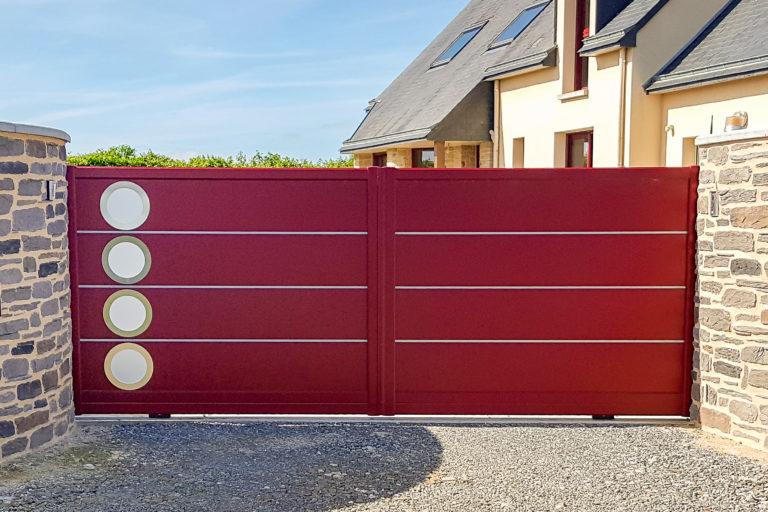 Portail coulissant en aluminium Rouge avec liseré décoratif en aluminium et hublots en inox