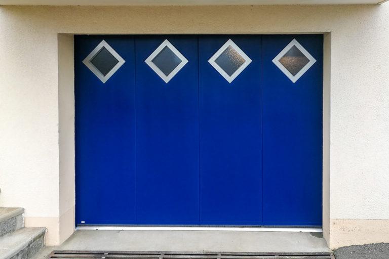 Porte de garage latérale en aluminium bleu avec hublots losange inox